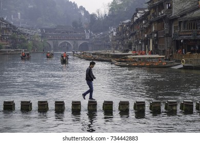 Asian man tourist wear black leather jacket and crossing the stepping stone bridge across the Tuojiang River in Fenghuang.  Located in Fenghuang County, Southwest of Hunan Province, China