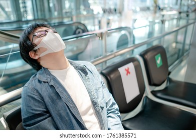 Asian man tourist wearing protective face mask feeling tired sitting in airport terminal. Social distancing in public transportation building.