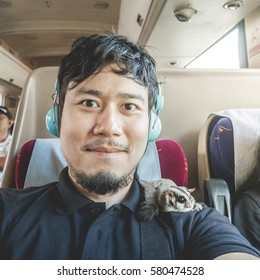 Asian man in a train seat take selfie photo on his travel trip.