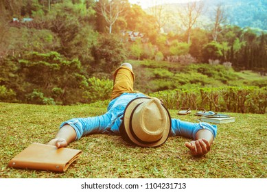 Asian man travel nature. Travel relax. sleep on the lawn in the park. in summer.