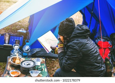 Asian man  travel relax camping in the holiday. camping on the Mountain. sit relax view map travel on the chair. Thailand