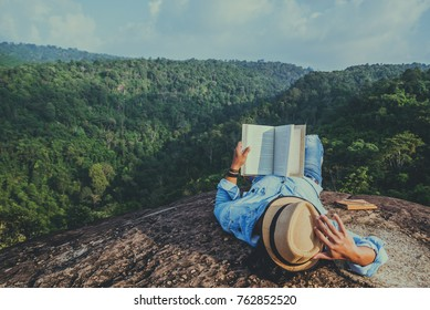 Asian man travel relax in the holiday. sleep relax read books on rocky cliffs. On the Moutain. In Thailand