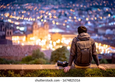 Asian man traveler and photograpaher sitting on viewpoint looking at illuminated cusco city at night. Cusco (Cuzco) is a city in southeastern Peru, near the Urubamba Valley of the Andes mountain range