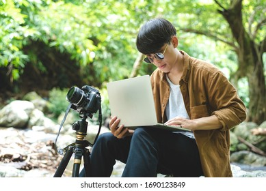 Asian man traveler photographer are taking photo and use laptop at beautiful forest. Travel photography, blogger, vlogger, camping, work aboard, adventure lifestyle, hipster, tourism concept.