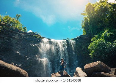 Asian man traveller use mobile phone near waterfall view. Waterfall in the rainforest under blue sky.