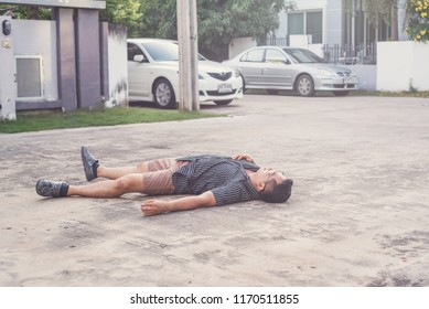 Asian man unconscious on the road. suffering from chest pain, having heart attack.Medicine and healthcare concept