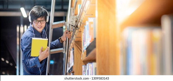 Asian man university student choosing book from bookshelf while standing on the ladder in library for education research. Bestseller collection in bookstore. Scholarship or educational opportunity