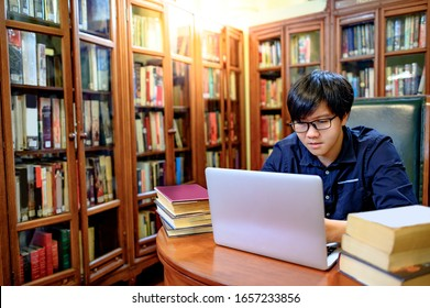 Asian man university student using laptop computer and reading book nearby vintage bookcase or bookshelf in college library. Textbook resources for education research. Scholarship opportunity concept