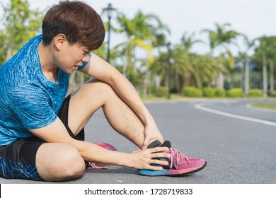 Asian man use hands hold on his ankle while running on road in the park. Injury from workout concept.