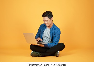 Asian man use of the laptop computer against color orange background