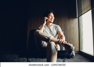 Asian man use smartphone in the dark corner of the room.