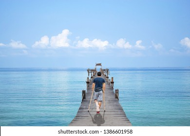 Asian man used wooden crutches walks on  bridge pier boat in the summer sea and the bright sky at Koh Kood, Trat in Thailand.