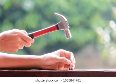 Asian man using hammer and nail on wood, Soft focus with blurred background.