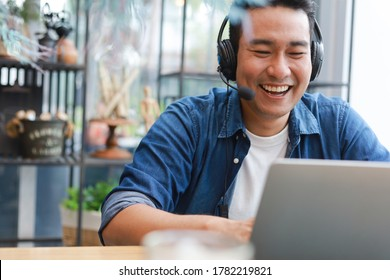 Asian man using laptop computer in coffee shop cafe smile and happy