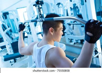 asian man using lat pulldown machine in gym