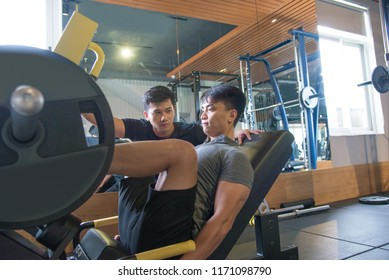 Asian man using leg press machine with personal trainer. Focused young guy training in gym. Bodybuilding concept.