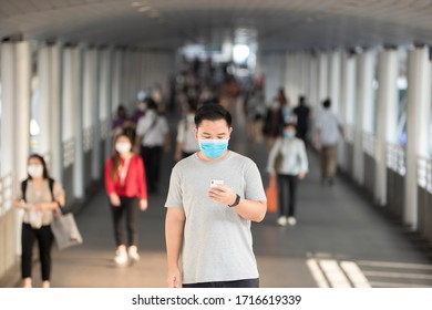 An Asian man is using a mobile phone. During the outbreak of covic-19 that became necessary during the outbreak of the virus