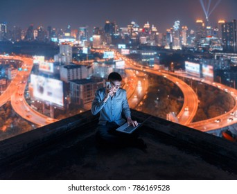 Asian man using phone and laptop with city  background, technology communication concept