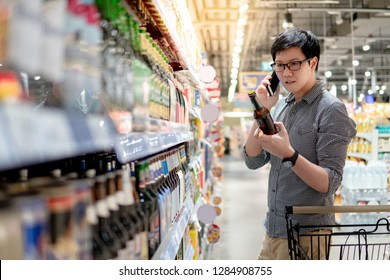 Asian man using phone shopping beer in supermarket. Male shopper with shooping cart choosing beer bottle in grocery store.