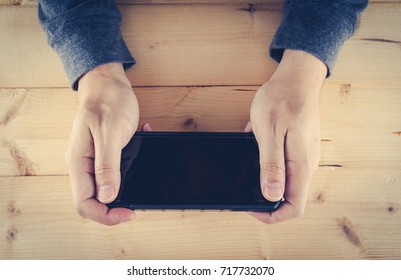 asian man using smart phone on wooden table