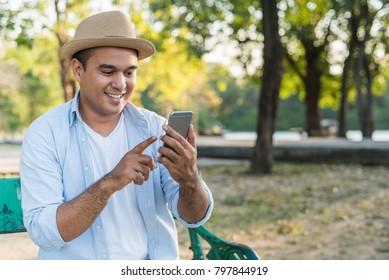 Asian man using smartphone in park