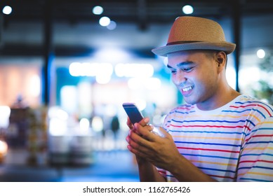 Asian man using smartphone at urban city in the night with bokeh lights.