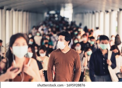 Asian man walking and standing between Crowd of blurred unrecognizable business people wearing surgical mask for prevent coronavirus Outbreak in rush hour working day at Bangkok transportation