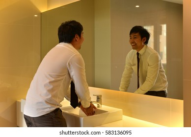An Asian man washing hands in bathroom, looking at luxury restroom, person