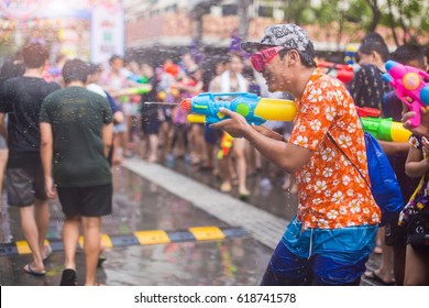 Asian man with water gun wearing summer shirt in Songkran festival (water festival), Thailand.