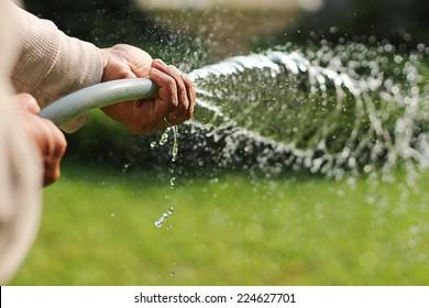 A asian man watering grass in the garden  in summer.