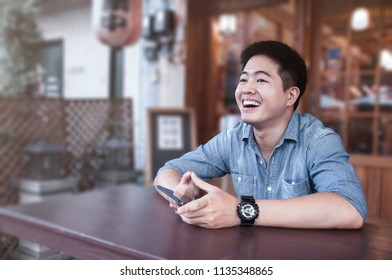 Asian man wear denim shirt laughing in front of Japanese food restaurant, Happy Man holding smart phone, A man  smiling with his happy time at Japanese restaurant