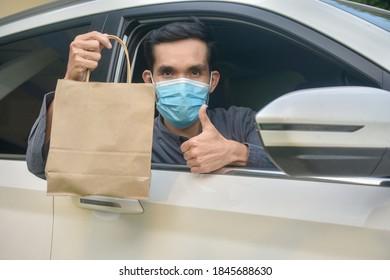 Asian man wear face mask holding shopping bag sitting in car,Mask protect coronavirus covid 19