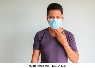 Asian man wear surgeon mask , hand touch the throat feeling pain and uncomfortable. White background