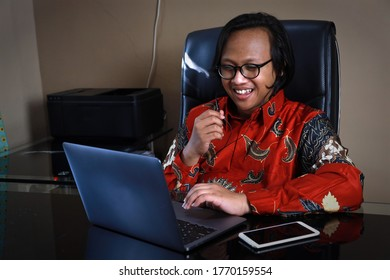 An Asian man wearing batik is laughing while doing a video conference