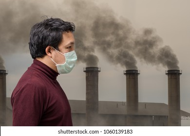 Asian man wearing the face mask against air pollution with hand catching the headache over over the Smokestack Factory with black smoke on the sky with cloud, healthcare industry and pollution concept
