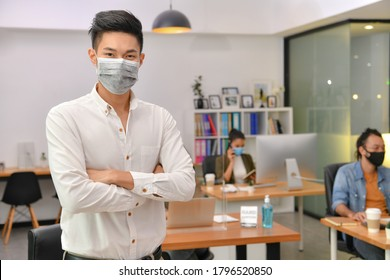 Asian man wearing face mask smile and looking at camera working in new normal office and doing social distancing during corona virus covid-19 pandemic