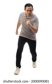 Asiatischer Mann mit grauem Hemd schwarz denim und weiße Schuhe, sieht die Kamera ernst, bereit zum Laufen, Frontansicht. Ganzes Körperporträt einzeln ausgeschnitten