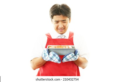 Asian man wearing kitchen apron with pound cake
