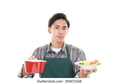 Asian man wearing kitchen apron