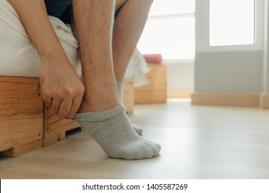 Asian man is wearing socks into his feet in the bedroom. Concept of getting ready and dress up.