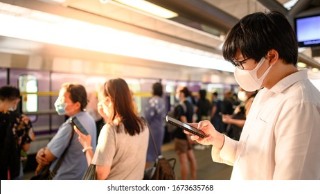 Asian man wearing surgical face mask using smartphone at skytrain station platform. Wuhan coronavirus (COVID-19) outbreak prevention in public transportation. Health awareness for pandemic protection