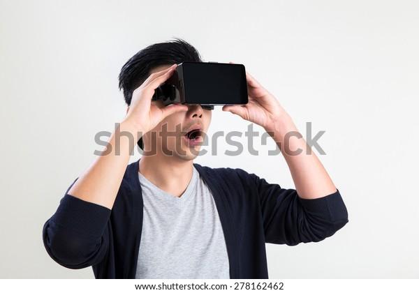 A asian man wearing virtual reality goggle.
