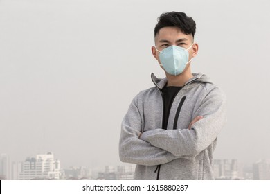 asian man wears protective n95 mask against air pollution or transmissible infectious diseases in the city