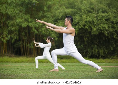 Asian Man and woman doing Tai Chi in a garden. Healthy lifestyle and relaxation concept.