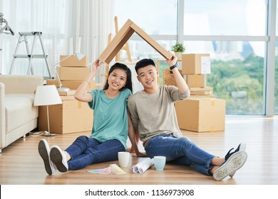 Asian man and woman sitting on floor of new apartment with charts and beverage holding cardboard pizza box above heads in roof style and looking at camera smiling with packed moving cartons on backgro