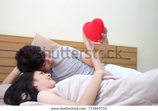 Asian man and woman sleep together in bed. Husband and wife holding red heart ball together in bedroom .  Lover concept, 20s age