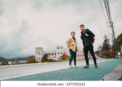 Asian man and woman are traveling at Chuzenji Lake, Nikko, Toshiba, Japan, in autumn.