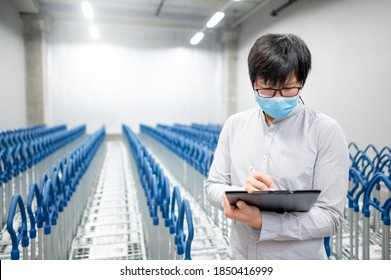 Asian man worker wearing face mask doing stocktaking in warehouse by using clipboard. Physical inventory count and preventing the spread of COVID-19 (Coronavirus).
