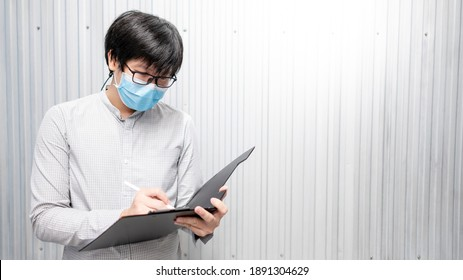 Asian man worker wearing face mask doing stocktaking in warehouse by using clipboard. Physical inventory count and preventing the spread of COVID-19 (Coronavirus)