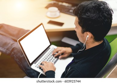 Asian man working about engineering design on his laptop while listening music in selective focus.